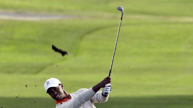 Tiger Woods sends a divot flying as he hits his approach to the 18th hole of the South Course during the first round of the Farmers Insurance Open golf tournament on Thursday, Jan. 24, 2013, in San Diego. Woods' shot went long into a bunker but he saved his par.  (AP Photo/Lenny Ignelzi)