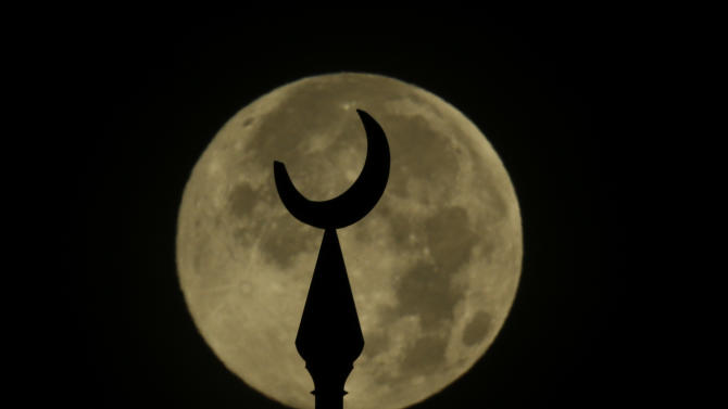 "A super moon sets behind the top of one of the minarets at the University of Tampa Sunday, June 23, 2013, in Tampa, Fla. The larger than normal moon called the ""Supermoon"" happens only once this year as the moon on its elliptical orbit is at its closest point to earth and is 13.5 percent larger than usual. (AP Photo/Chris O'Meara)"