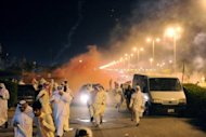 Protesters run for cover as Kuwait riot police use stun grenades and tear gas to disperse thousands of demonstrators in Kuwait City on October 31. Kuwait on Thursday released on bail opposition leader Mussallam al-Barrak after a night of violent protests against his detention that left dozens hurt, his lawyer and an AFP photographer said