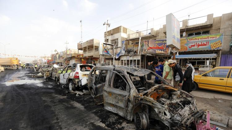 Residents look at the scene of a car bomb explosion in Baghdad's Habibiya district