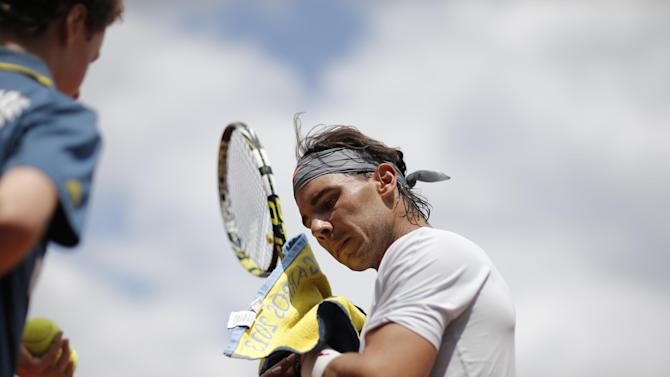 A ball boy waits as Spain's Rafael Nadal wipes his face in his first round match against Germany's Daniel Brands of the French Open tennis tournament, at Roland Garros stadium in Paris, Monday, May 27, 2013. (AP Photo/Christophe Ena)