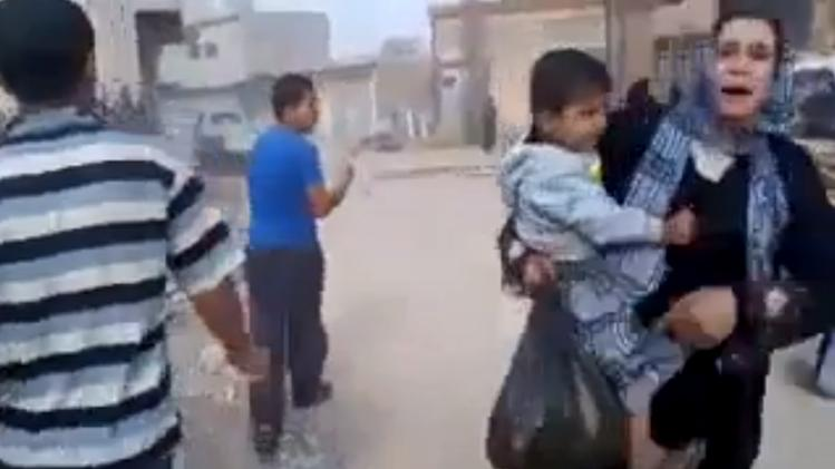This image taken from video obtained from Shaam News Network, which has been authenticated based on its contents and other AP reporting, shows a woman carrying a child running away from the scene of shelling in Qouriyeh, Syria, Friday, Nov. 9, 2012. (AP Photo/Shaam News Network via AP video)