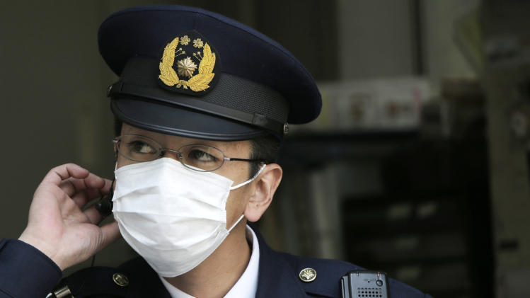 In this photo taken March 16, 2013, a police officer wearing a mask is on duty at a police station in Tokyo. Japan is becoming a sea of surgical masks. It's about pollen, about germs and even a little about China, its polluting rival across the sea. (AP Photo/Itsuo Inouye)