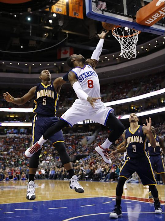 Philadelphia 76ers' Tony Wroten (8) goes up to shoot against Indiana Pacers' Lavoy Allen (5) and George Hill (3) during the second half of an NBA basketball game on Friday, March 14, 2014, in