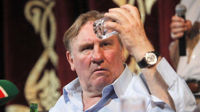 French actor Gerard Depardieu looks at a glass during a news conference in Chechnya's provincial capital Grozny, Russia, Tuesday, May 21, 2013. Depardieu announced his plans to star in a drama about a Chechen man investigating and avenging the death of his son in Moscow. (AP Photo/Musa Sadulayev)