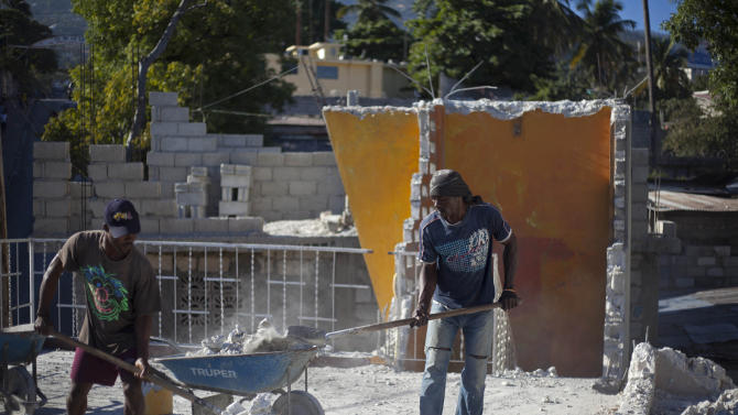 Edner Gue, right, and Labon Florestal work to clean up the earthquake damaged Grande College Auguste Comte de Petionville, in their neighborhood of Petionville, Haiti, Friday, Jan. 11, 2013.  The director of the elementary and high school is paying workers to clean up his school and plans to open classes even if the government does not rebuild it. On Saturday, Haiti will mark the 3rd anniversary of the earthquake that officials say killed more than 300,000 people and displaced more than a million others. The disaster is regarded as one of the worst natural disasters in modern history. (AP Photo/Dieu Nalio Chery)
