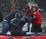 Residents, including a young child, are rescued by emergency personnel from flood waters brought on by Hurricane Sandy in Little Ferry, New Jersey, October 30, 2012. REUTERS/Adam Hunger