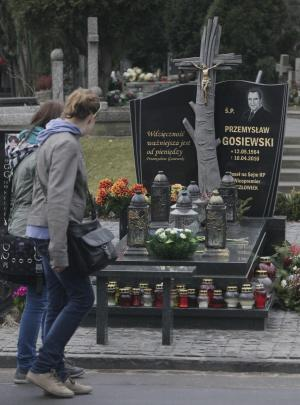 People walk by the grave of Przemyslaw Gosiewski, a Polish lawmaker who was killed in Russia in 2010 along with President Lech Kaczynski, in Warsaw, Poland, on Wednesday, March 21, 2012. Gosiewski's remains were exhumed on Monday so a new autopsy can be performed on them due to reported mistakes in an initial Russian forensic investigation. Gosiewski is one of three of the 96 people killed in the April 2010 crash whose remains are being submitted to new autopsies due to alleged mistakes in the Russian documentation. (AP Photo/Czarek Sokolowski)