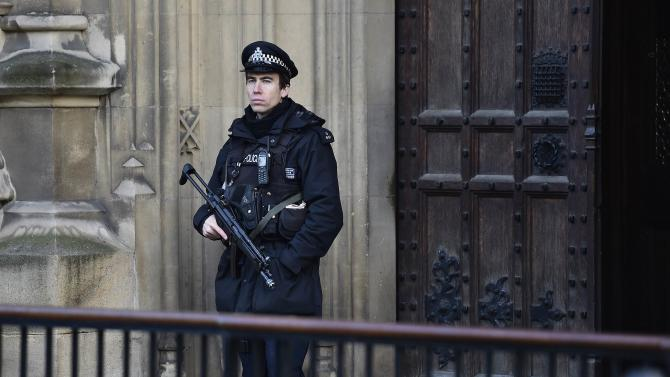 An armed police officer guards outside of the Houses of Parliament in central London