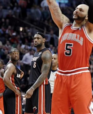 Miami Heat guard Dwyane Wade, left, and forward LeBron James, watch Chicago Bulls forward Carlos Boozer shoot a free throw after James fouled him during the fourth quarter of an NBA basketball game in Chicago on Wednesday, March 27, 2013. The Bulls won 101-97, ending the Heat's 27-game winning streak. (AP Photo/Nam Y. Huh)