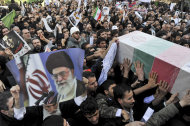 "Beside a poster of Iranian supreme leader Ayatollah Ali Khamenei, mourners carry a flag draped coffin of Mostafa Ahmadi Roshan, a chemistry expert and a director of the Natanz uranium enrichment facility in central Iran, who was killed in a brazen daylight assassination when two assailants on a motorcycle attached a magnetic bomb to his car Wednesday, in his funeral ceremony, on Friday, Jan. 13, 2012, in Tehran, Iran. Thousands of mourners chanted ""Death to Israel"" and ""Death to America"" on Friday during the funeral of a slain nuclear expert whom Iranian officials accuse the two nations of killing in a bomb blast this week as part of a secret operation to stop Iran's nuclear program. (AP Photo/Iranian Students News Agency, Mehdi Ghasemi)"