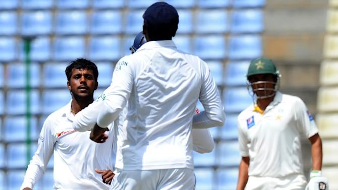 Sri Lanka's Tharindu Kaushal (L) celebrates with his teammates after he dismisses Pakistan's Shan Masood during the final day of the third and final Test in Pallekele on July 7, 2015