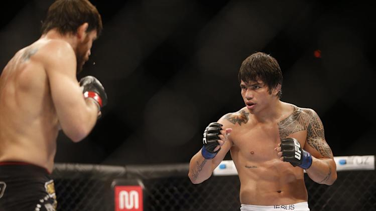 FILE - In a Oct.14, 2012 file photo, Erick Silva, right, from Brazil, fights Jon Fitch, left, from the United States, during their welterweight mixed martial arts bout at the Ultimate Fighting Championship (UFC) 153 in Rio de Janeiro, Brazil. On Saturday, May 10, 2014, Sliva was taken out on a stretcher at the end of a fight against Ohio native Matt Brown and then to a Cincinnati hospital for evaluation. Ultimate Fighting Championship President Dana White told reporters soon after the fight that Erick Silva would be examined for a possible concussion and fractured jaw. There was no update available immediately Sunday from the UFC on the Brazilian fighter's condition. (AP Photo/Felipe Dana, File)