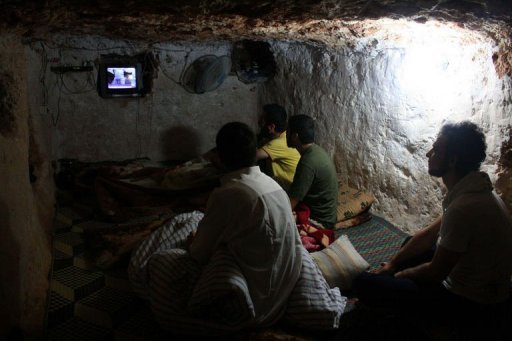 "Syrians watch TV at an underground shelter in Al-Bueda, 12 kms from the flashpoint city of Homs. The spike in violence in Syria has triggered alarm bells in Jordan that it could be dragged into the conflict with ""severe"" repercussions, analysts say"