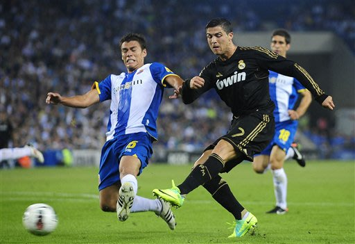 In this Oct. 2, 2011 file photo, Espanyol's Hector Moreno, from Mexico, , left, duels for the ball against Real Madrid's Cristiano Ronaldo, from Portugal during a Spanish La Liga soccer match at Corne