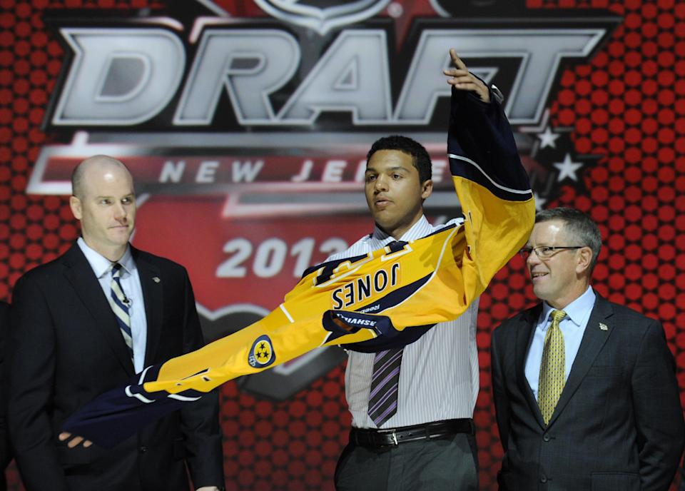 Seth Jones, a defenseman, pulls on a Nashville Predators sweater after being chosen 4th overall in the first round of the NHL hockey draft, Sunday, June 30, 2013, in Newark, N.J. (AP Photo/Bill Kostroun)