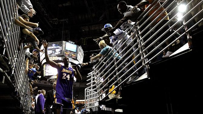 Fans greet Los Angeles Lakers shooting guard Kobe Bryant (24) as he walks off the court after an NBA basketball game against the New Orleans Hornets in New Orleans, Wednesday, Dec. 5, 2012. Bryant became the youngest player in NBA history to surpass 30,000 points. The Lakers won 103-87. (AP Photo/Gerald Herbert)