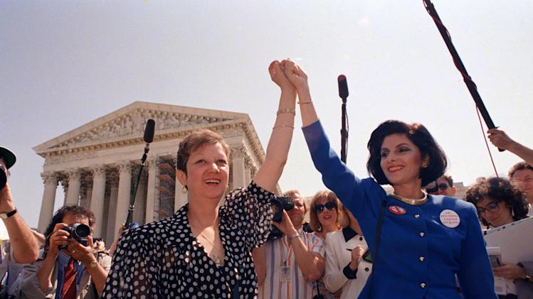 FILE - In this Wednesday, April 26, 1989 file photo, Norma McCorvey, Jane Roe in the 1973 court case, left, and her attorney Gloria Allred hold hands as they leave the Supreme Court building in Washington after sitting in while the court listened to arguments in a Missouri abortion case. Months later, the high court ultimately upheld the Missouri law in the case, Webster v. Reproductive Health Service, making it illegal to use public officials or facilities for abortions. (AP Photo/J. Scott Applewhite, File)