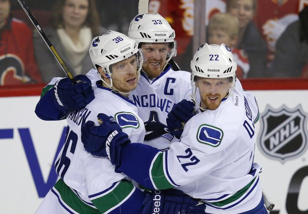 Vancouver Canucks' Hansen celebrates his goal with the Sedin brothers during their NHL hockey game against the Calgary Flames in Calgary.