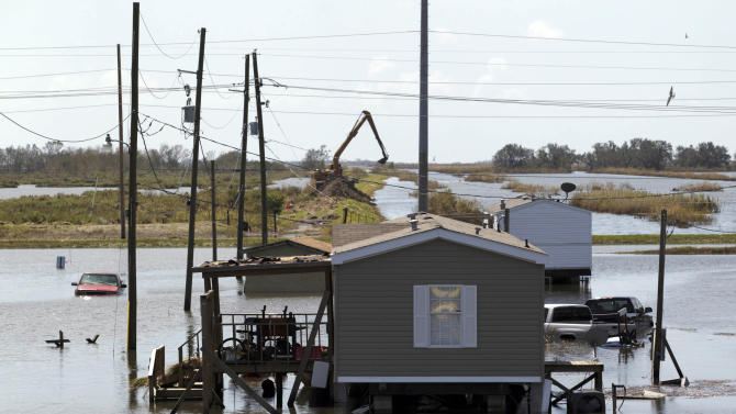 Trucks are flooded in receding flood waters from Hurricane Isaac along Louisiana Hwy 23 near West Point a La Hache, La., in Plaquemines Parish  Monday, Sept. 3, 2012. (AP Photo/Matthew Hinton)