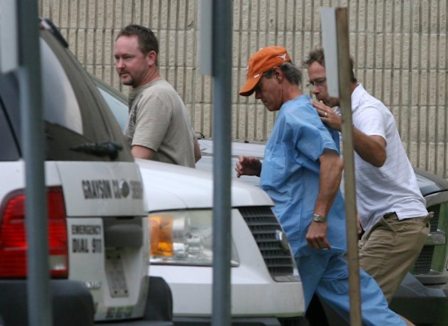 Randy Travis, center wearing cap, exits the Grayson County jail with two unknown persons Wednesday Aug. 8, 2012, in Sherman, Texas, after being arraigned on charges of driving while intoxicated and retaliation. (AP Photo/The Herald Democrat, Chris Jennings) TV OUT; MAGS OUT; TV AND MAGAZINE CALL FOR RATES TERMS;MANDATORY CREDIT