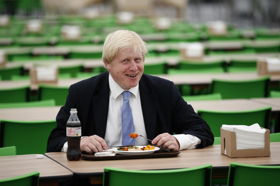 The mayor of London Boris Johnson poses for the media with a plate of food in the athletes' dining hall during a media opportunity at the Olympic and Paralympic athlete's village in London, Thursday, July 12, 2012.  The London Olympics begin on July 27. (AP Photo/Matt Dunham)