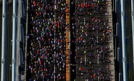Runners cross the Verrazano-Narrows Bridge toward Brooklyn at the start of the 2011 New York City marathon: This year's race will reportedly go on despite the storm's destruction.