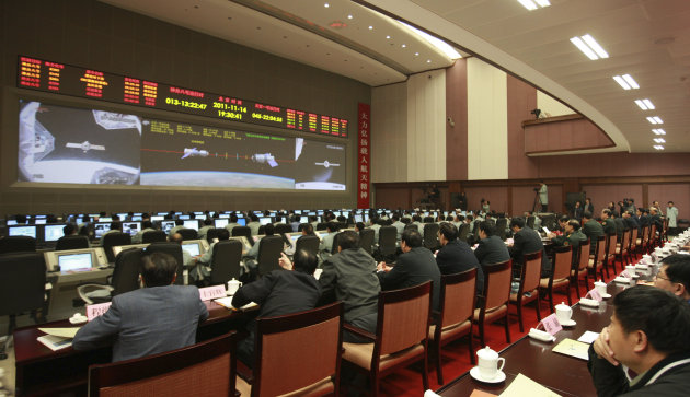 In this photo released by China's Xinhua News Agency, staff members monitor the process of re-docking of China's Shenzhou-8 unmanned spacecraft with the Tiangong-1, a module of the country's planned space lab, in the Beijing Aerospace Flight Control Center in Beijing on Monday, Nov. 14, 2011. China said the two unmanned spacecraft have docked successfully in space for a second time Monday. (AP Photo/Xinhua, Wang Jianmin) NO SALES