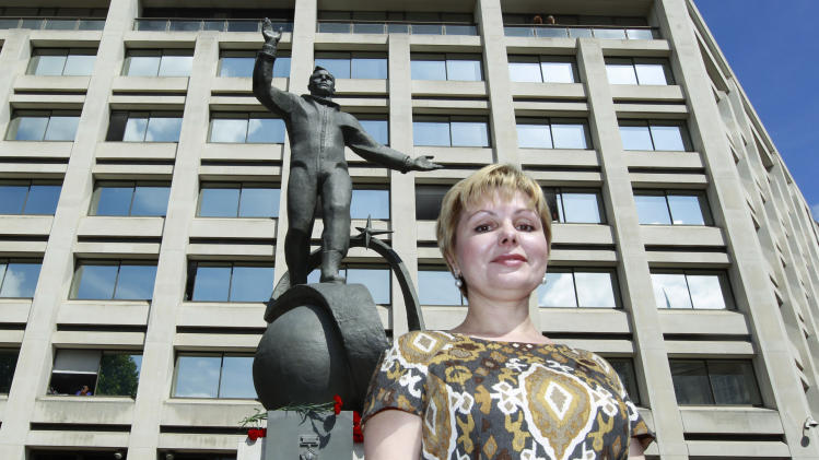 Elena Gagarina, director of the Kremlin Museums in Moscow, and daughter of Yuri Gagarin, the first man in space, poses in front of a newly-unveiled statue of her father, outside the headquarters of the British Council, in central London, Thursday, July 14, 2011.  A gift from the Russian Space Agency (Roscosmos) to the British Council, the statue shows Gagarin standing on a globe in his space suit, and it will be installed at this location for a period of 12 months to mark the 50th anniversary of the first manned space flight. (AP Photo/Lefteris Pitarakis)