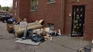 Damaged furniture sits outside the apartment buildings on Woodward Avenue.
