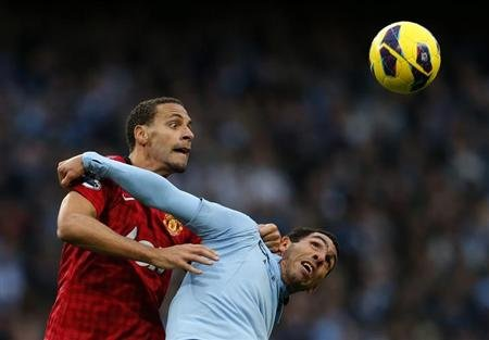 Manchester City's Tevez challenges Manchester United's Ferdinand during their English Premier League soccer match at Etihad Stadium in Manchester