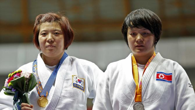 Gold medallist Jeong of South Korea poses with silver medallist Sol of North Korea after the women's -78 kg judo event during the 17th Asian Games in Incheon
