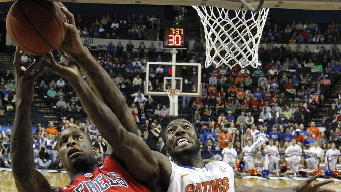 Florida center Patric Young (4) vies for a rebound with Mississippi forward Murphy Holloway (31) during the first half of an NCAA college basketball game in the final round of the Southeastern Conference tournament, Sunday, March 17, 2013, in Nashville, Tenn. (AP Photo/John Bazemore)