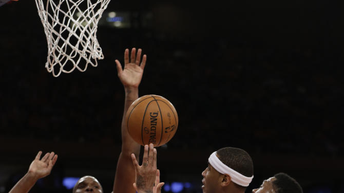Miami Heat forward Udonis Haslem, right, holds New York Knicks forward Carmelo Anthony, center, as Heat center Chris Bosh (1) tries to block Anthony's shot during the first half of their an basketball game at Madison Square Garden in New York, Sunday, March 3, 2013. A foul was called on Haslem. (AP Photo/Kathy Willens)