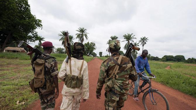 In this photo taken July 15, 2013, Seleka rebels walk in the town of Bria, Central African Republic. Central African Republic's rebel leader-turned-president, Michel Djotodia, who was sworn into office on Sunday, Aug. 18, five months after seizing power, has pledged to return the country to democracy and stability. But Djotodia's Seleka rebels, who overthrew the previous president in March, are accused of continuing to carry out atrocities in some of the most isolated corners of this deeply impoverished country in the heart of Africa. (AP Photo/Jacob Zocherman)