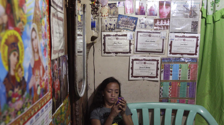 In this photo taken Dec. 4, 2012, Filipino slum dweller Jessa Balote uses her smartphone beside a wall filled with her ballet certificates and pictures inside her cramped home at a place called Aroma in Tondo, Manila, Philippines. Balote, who used to tag along with her family as they collect garbage at a nearby dumpsite, is a scholar at Ballet Manila's dance program. As an apprentice, she makes around 7,000 pesos ($170) a month, sometimes double that, from stipend and performance fees. (AP Photo/Aaron Favila)
