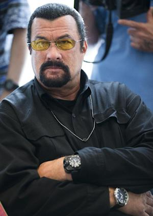 File- This June 2, 2013, file photo shows actor Steven Seagal looking on as he waits for a news conference of U.S. Congressional delegation to Russia in U.S. Embassy in Moscow, Russia. The actor told KNXV-TV that he is considering a shot at Arizona's highest office and has had a talk about the bid with the self-proclaimed toughest sheriff in America. (AP Photo/Alexander Zemlianichenko, File)