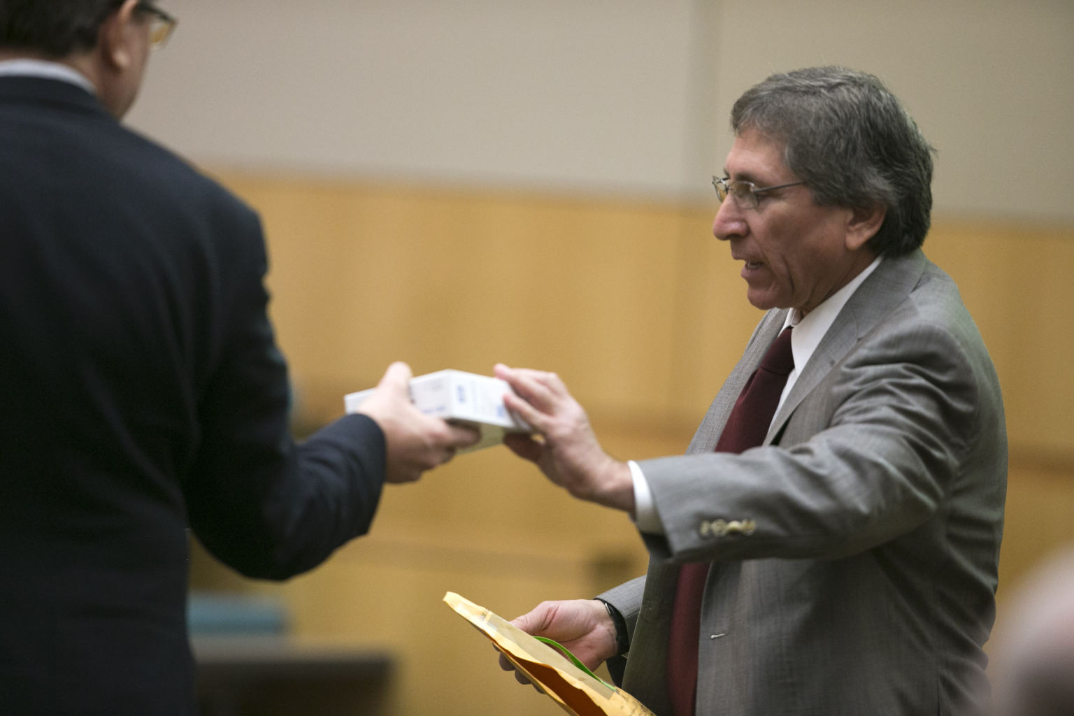 Prosecutor Juan Martinez, right, hands a hard drive that was brought ...