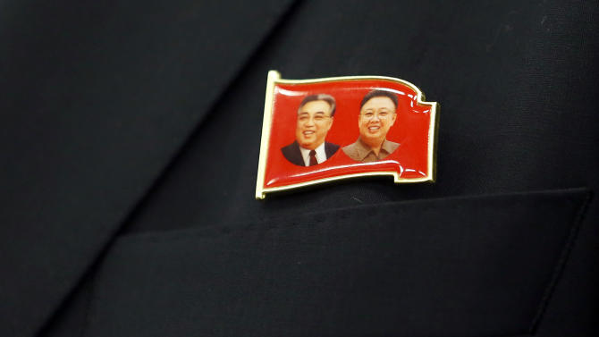 Pin worn by North Korea tourism representative Ri Yong Bom depicting former North Korean leaders Kim Il Sung and Kim Jong Il is seen in Bern
