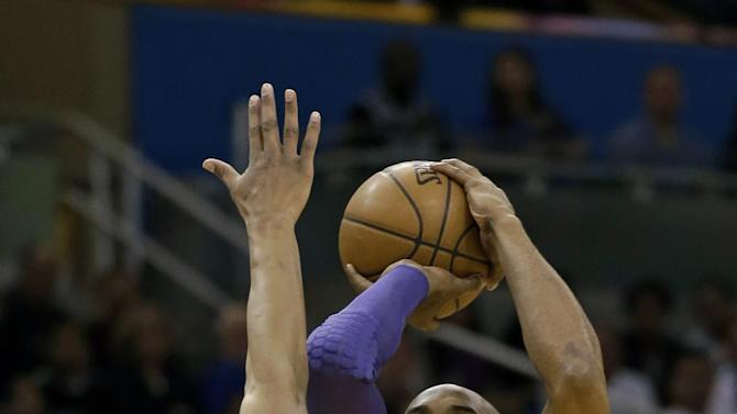Los Angeles Lakers' Kobe Bryant (24) takes a shot over Orlando Magic's Arron Afflalo (4) during the first half of an NBA basketball game, Tuesday, March 12, 2013, in Orlando, Fla. (AP Photo/John Raoux)