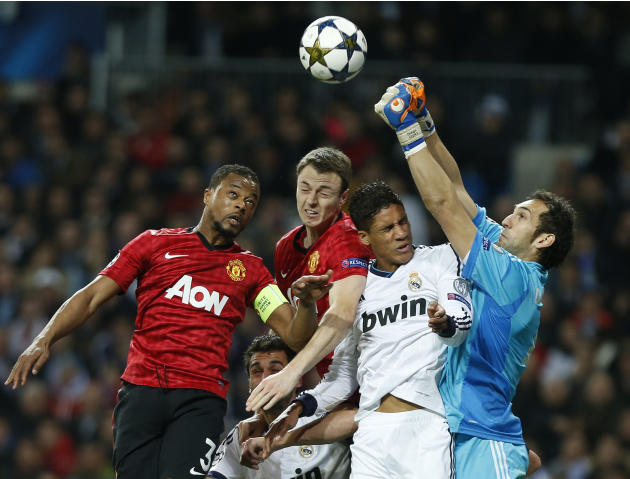 Manchester United's Patrice Evra, left, and Jonny Evans contest a high ball with Real Madrid's Raphael Varane from France and goalkeeper Diego Lopez, right, during the Champions League round of 16 fir