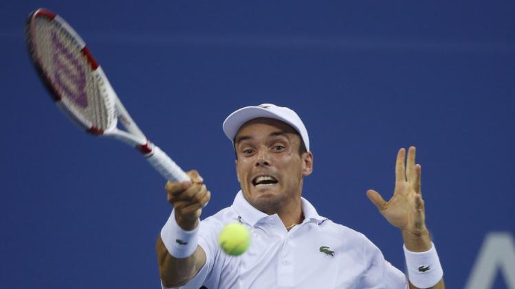 Roberto Bautista Agut of Spain returns a shot to Roger Federer of Switzerland during their men's singles match at the 2014 U.S. Open tennis tournament in New York