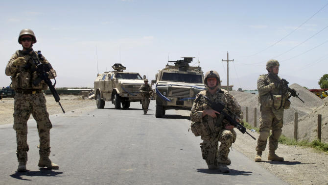 German soldiers with the NATO-led International Security Assistance Force (ISAF) guard a road close to the location of a suicide attack on a German military convoy, in Kunduz, north of Kabul, Afghanistan on Sunday, June 19, 2011. A suicide car bomber struck a German military convoy in northern Afghanistan on Sunday, detonating explosives that killed three Afghan civilians and overturned at least one armored vehicle, according to officials and witnesses. (AP Photo/Fulad Hamdard)