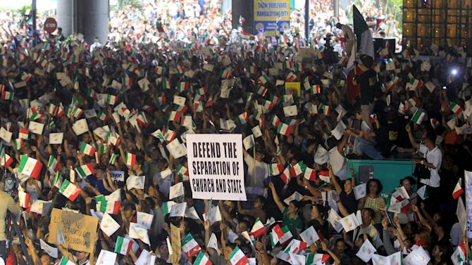 """Protesters belonging to the Iglesia ni Cristo (Church of Christ) group chant """"Justice"""" as they wave the group's flags during a rally along EDSA highway in Mandaluyong"""