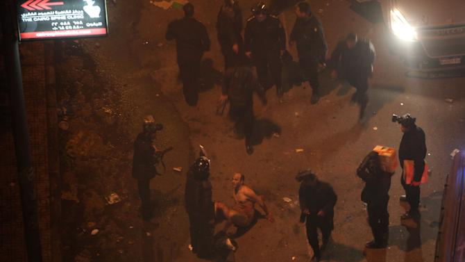Egyptian riot police beat a man, after stripping him during clashes next to the presidential palace, Friday, Feb. 1, 2013, in Cairo. Protesters denouncing Egypt's Islamist president hurled stones and firebombs through the gates of his palace gates on Friday, clashing with security forces who fired tear gas and water cannons, as more than a week of political violence came to Mohammed Morsi's symbolic doorstep for the first time. (AP Photo/Khalil Hamra)