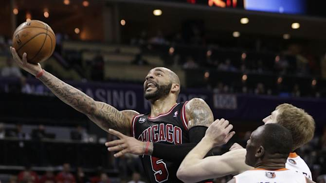 Chicago Bulls' Carlos Boozer (5) drives past Charlotte Bobcats' Bismack Biyombo (0) during the second half of an NBA basketball game in Charlotte, N.C., Wednesday, April 16, 2014. The Bobcats won 91-86 in overtime. (AP Photo/Chuck Burton)