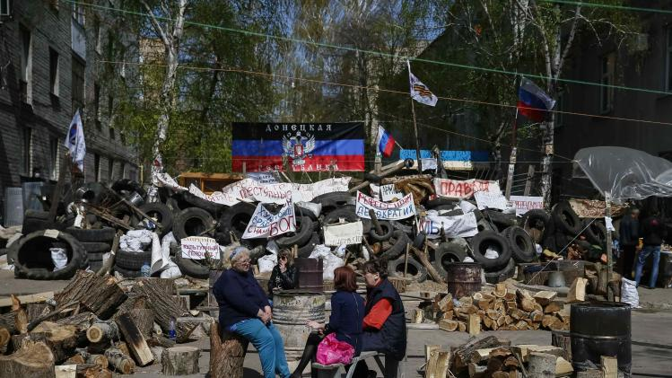 Pro-Russian protesters sit near barricades at the police headquarters in the eastern Ukrainian town of Slaviansk