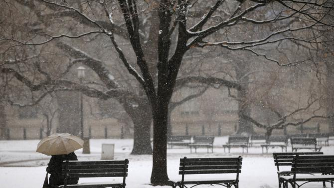 A woman sits on a park bench as snow falls in Lafayette Park near the White House in Washington