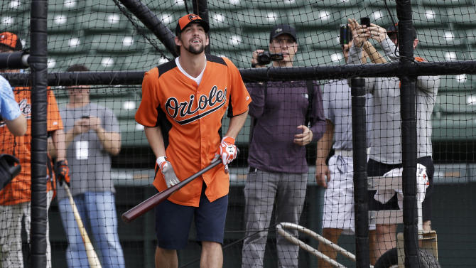 Former Olympic swimmer Michael Phelps watches a fly ball while hitting in the batting cage during a Baltimore Orioles baseball spring training workout Thursday, Feb. 21, 2013, in Sarasota, Fla.  Phelps, a native of Baltimore who was in the area filming his Golf Channel show The Haney Project, took batting practice with the team. (AP Photo/Charlie Neibergall)