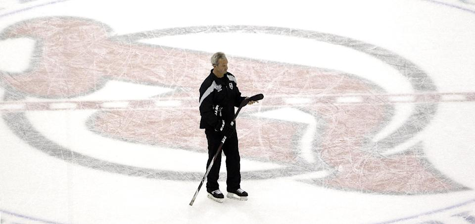 Los Angeles Kings head coach Darryl Sutter skates near the New Jersey Devils logo during practice in preparation for Wednesday's  Game 1 of the NHL hockey Stanley Cup Final series against the Devils, Tuesday, May 29, 2012, in Newark, N.J. (AP Photo/Julio Cortez)